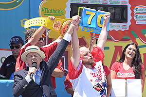 Nathan's Famous MC George Shea raises winner Joey Chestnut's