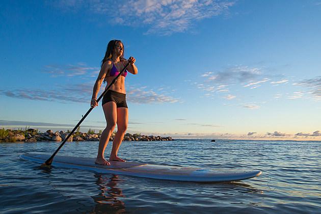 Female paddleboarding at sunrise